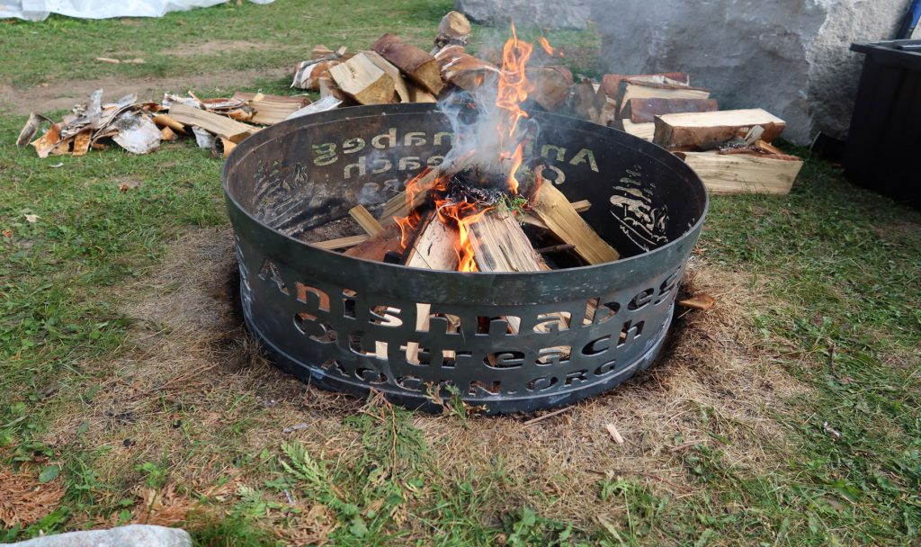 Firepit with anishnabeg outreach logo