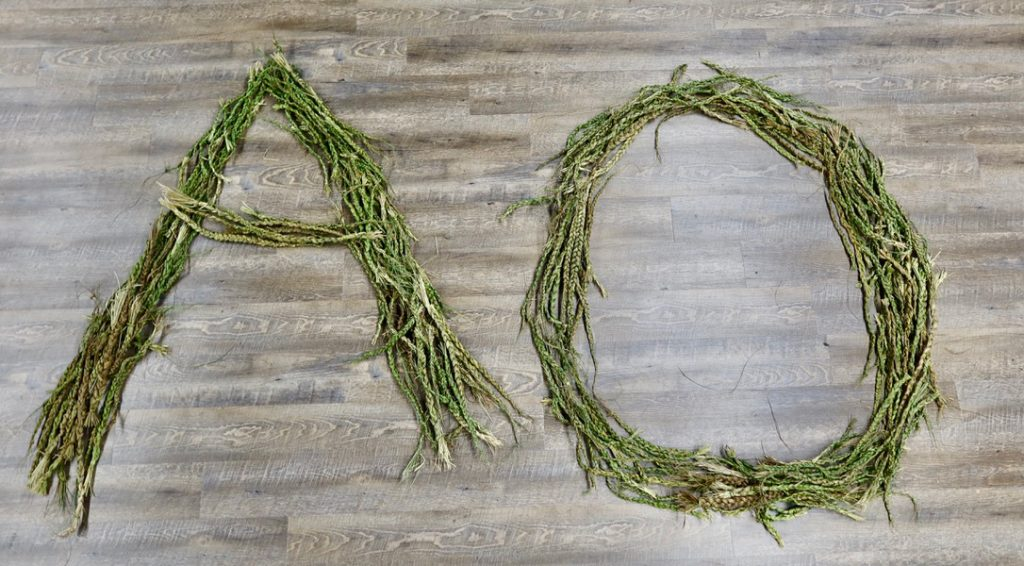The letters A and O spelt out using sweetgrass braids on the floor