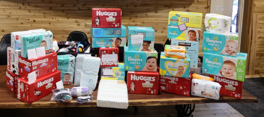 Donation of baby items on a table like diapers, wipes and socks.