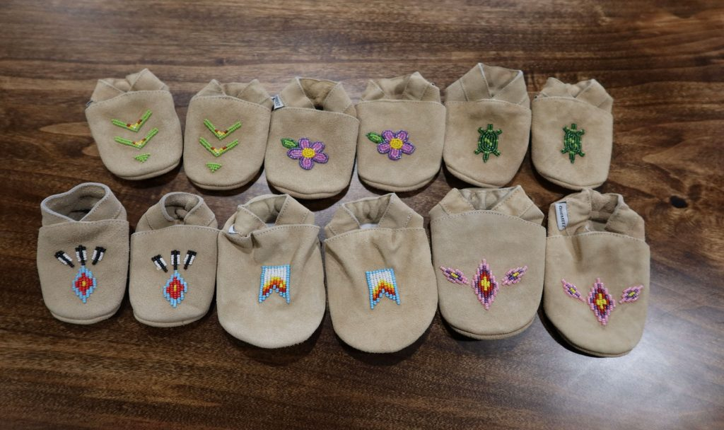 Baby moccasins with designs on the front like flowers and turtles