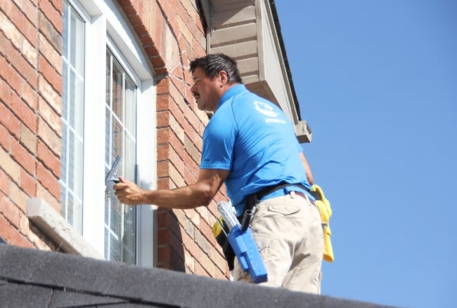 cleaning an outdoor window at a client's house