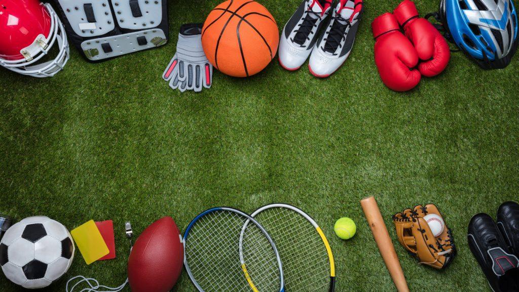 multiple sports equipment on grass like tennis rackets, soccer ball, football, baseball gloves, bike helmet.