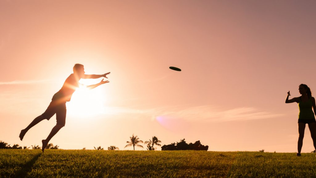 a person passing a frisbee to another player in the sunset