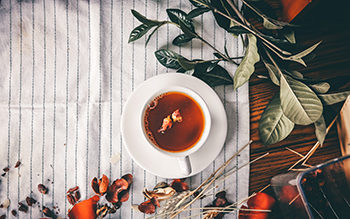 A cup of tea on a table with different herbs.